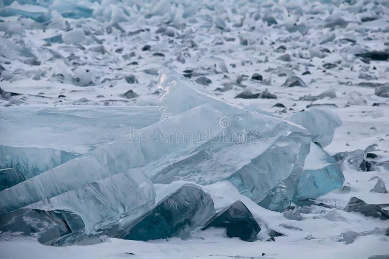 Gry i de blåa mindre kulle av is Lake Baikal, i ett snöig fält I arkivbilder