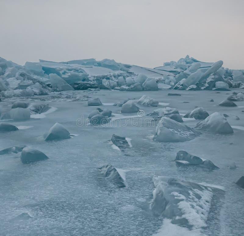 Gry i de blåa mindre kulle av is Lake Baikal, i ett snöig fält i vinter på en resa arkivfoto