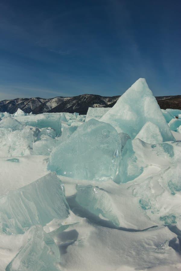 Gry i de blåa mindre kulle av is Lake Baikal, i ett snöig fält i vinter på en resa arkivbilder