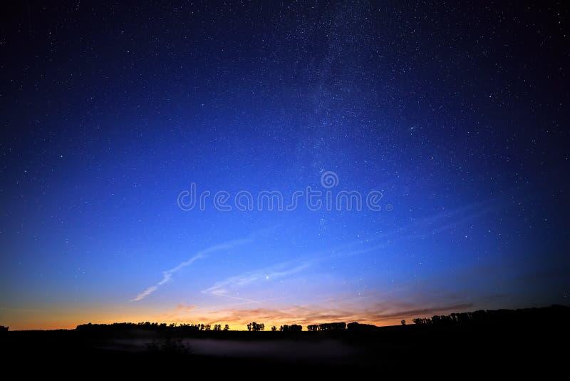 Gry på en stjärnklar bakgrundshimmel och Vintergatan royaltyfri fotografi