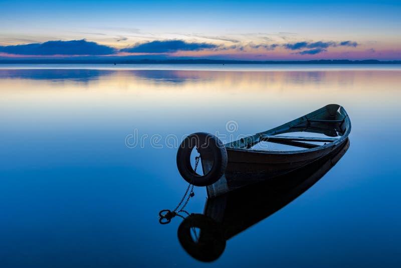 Gry på sjön Seliger med en gammal fiskebåt i förgrunden fotografering för bildbyråer