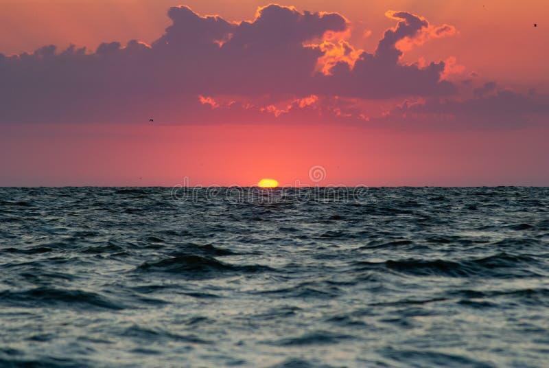Gry på vattnet, solen över horisonten, ett ljust glöd i himlen, royaltyfri foto