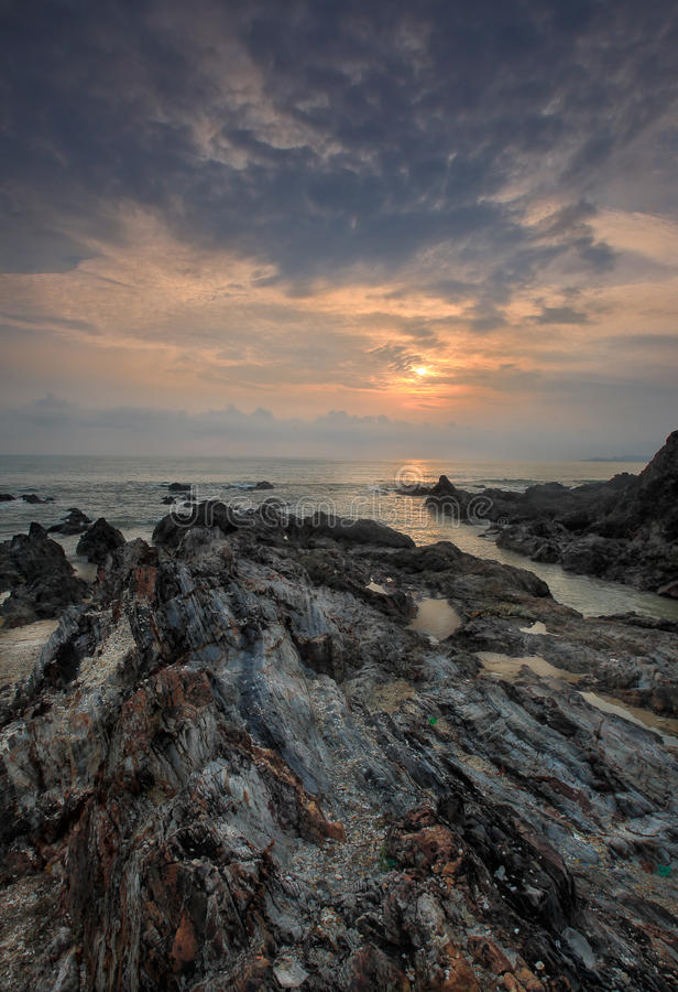 Gry sikten av sandstranden med rocks royaltyfri foto