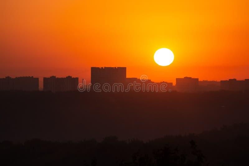 Gry solen på bakgrunden av avlägsna byggnader royaltyfri bild