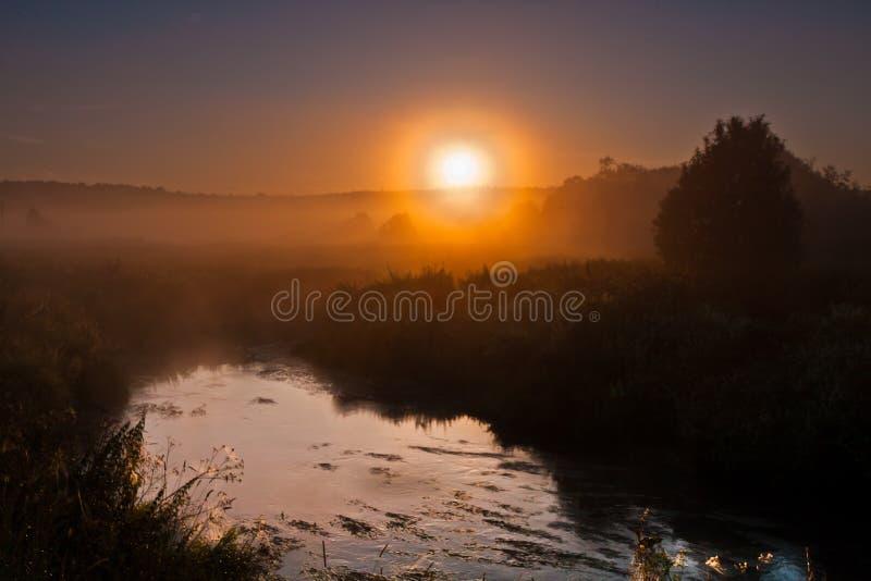 Gry, sollöneförhöjningarna över floden och gjort mörkare landskap som är ljust fotografering för bildbyråer