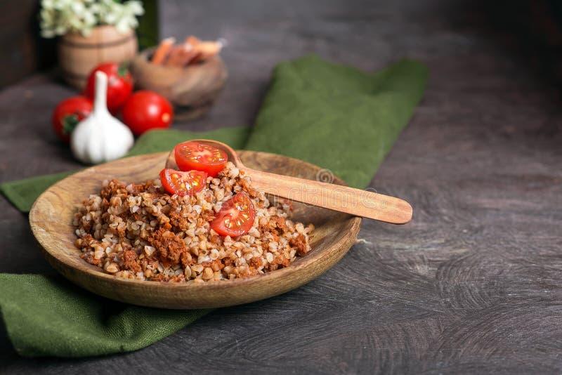 Gryczana owsianka z pomidorem na drewnianym talerzu fotografia stock