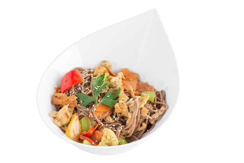 Gryczani kluski z kurczakiem i warzywami z teriyaki kumberlandem odizolowywającym na białym tle Gryczani kluski w białym talerzu obraz royalty free
