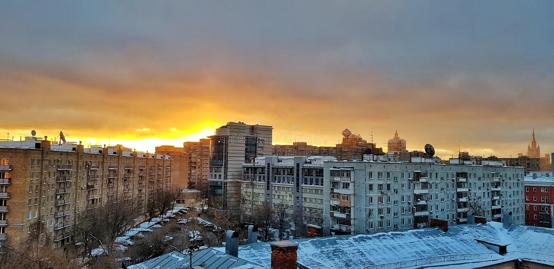 Gryning i Moskva över hus och en härlig stadssoluppgång reflekterad i fönstren av höghus och skyskrapor på en frostig vinter royaltyfria foton