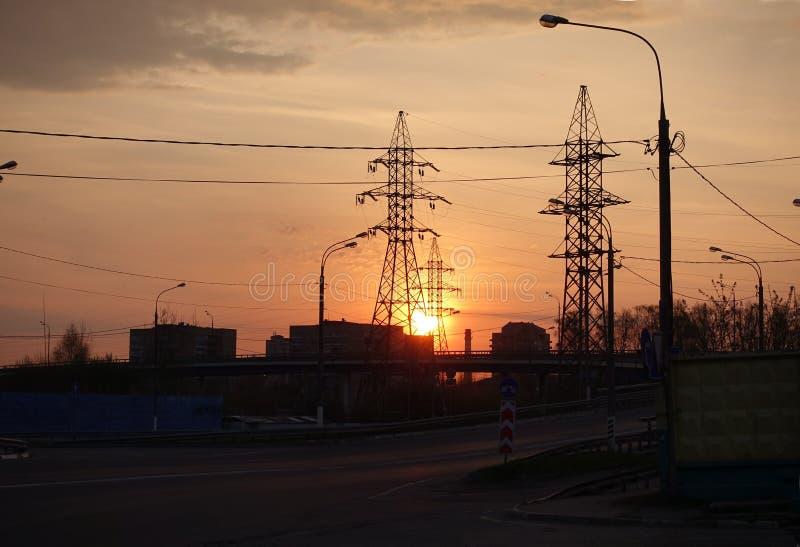 Gryning på bakgrunden av elektriska torn för höghus Soll?nef?rh?jningarna r?d sky ovanf?r den h?rliga naturen f?r morgonen f?r gu arkivbilder