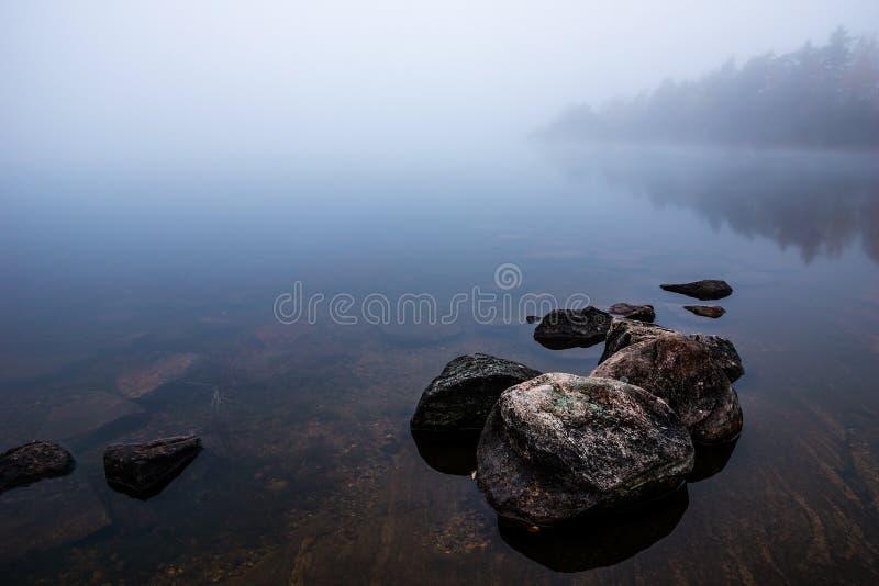 Gryning vid den dolda sjön för dimma fotografering för bildbyråer