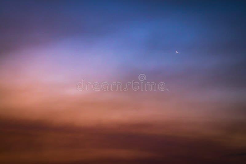 Gryninghimmel med månen arkivbilder