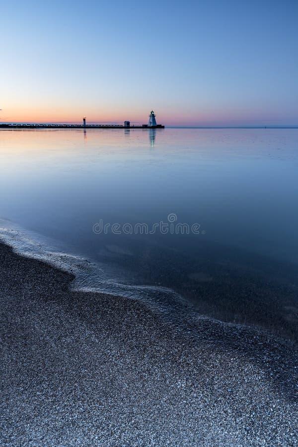 Gryningsoluppgång för stillhet färgar pre att reflektera på shoreline med lighth royaltyfri bild
