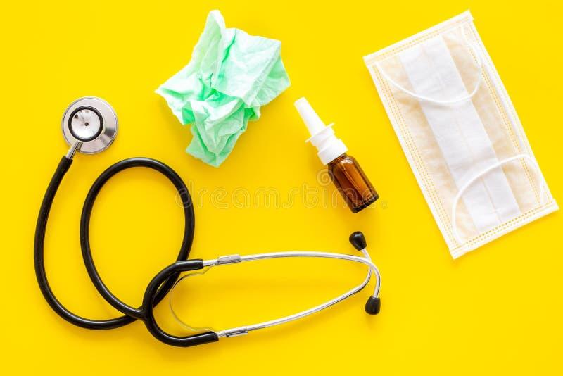 Grypa krople Działający nosa pojęcie Marszcząca pielucha blisko stetoskopu i twarzy maski na żółtego tła odgórnym widoku obraz stock