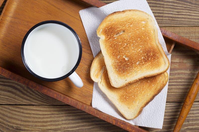 Grzanka chleb i emaliowy kubek mleko obrazy royalty free