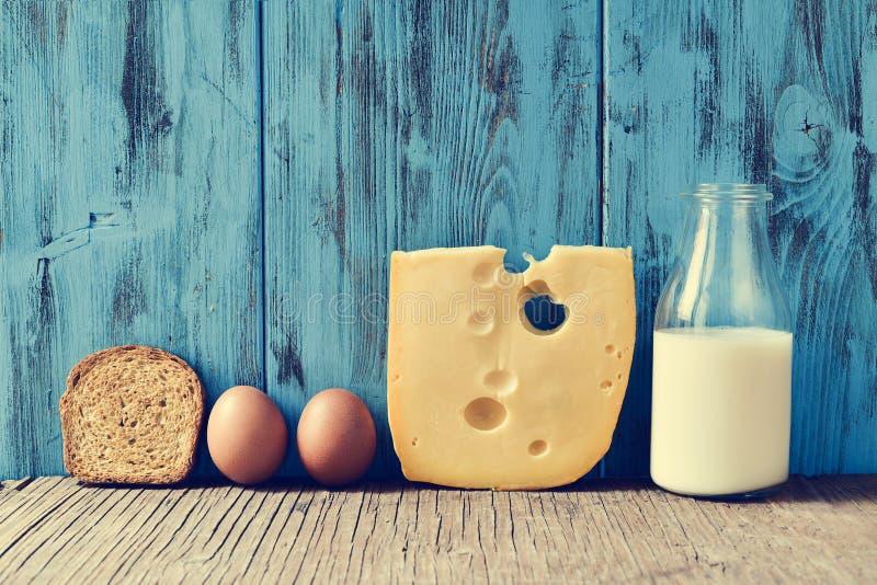 Grzanka, jajka, ser i mleko na nieociosanym drewnianym stole z fi, obrazy royalty free
