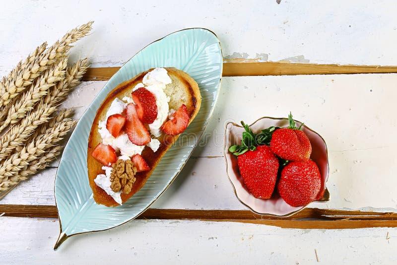 Grzanka lub bruschetta z truskawką na kremowym serze na białym drewnianym tle, kopii przestrzeń, odgórny widok, set obrazy stock