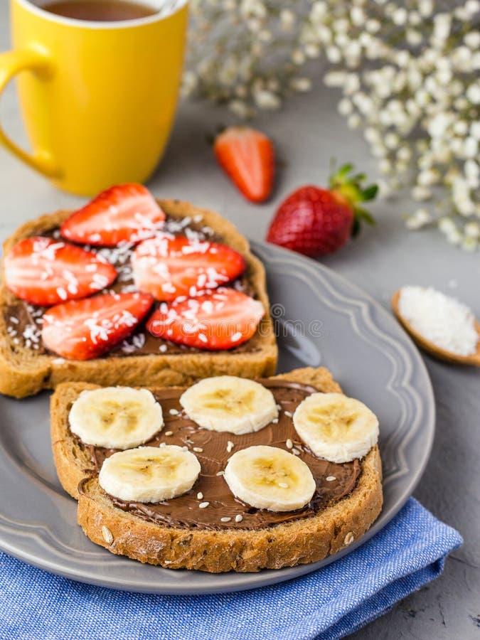 Grzanka z czekolad? i owoc na szaro?? talerzu Truskawki i banany na kamiennym kuchennego sto?u tle Odg?rny widok obrazy royalty free