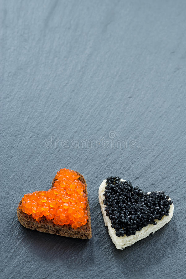 Grzanka z czerwonym i czarnym kawiorem w postaci serca zdjęcie royalty free