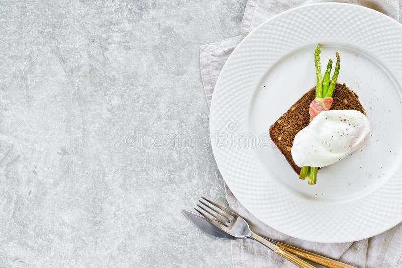 Grzanka z k?usuj?cym jajecznym i piec na grillu mini asparagusem w bekonie Szary t?o, odg?rny widok, przestrze? dla teksta obraz royalty free