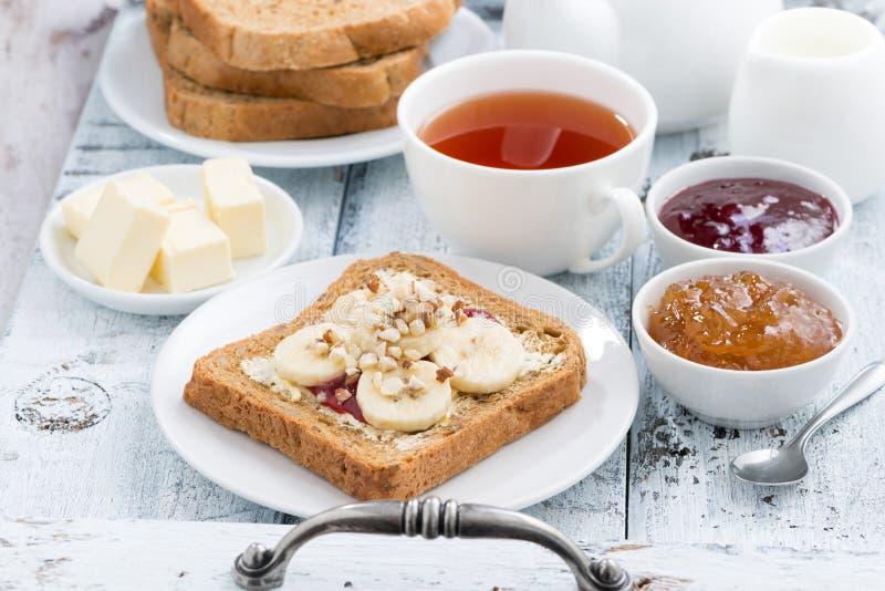 Grzanka z masłem orzechowym i bananem, świeża czarna herbata obraz royalty free