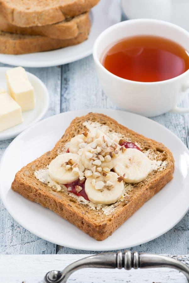 Grzanka z masłem orzechowym i bananem, świeża czarna herbata, vertical, odgórny widok zdjęcia stock