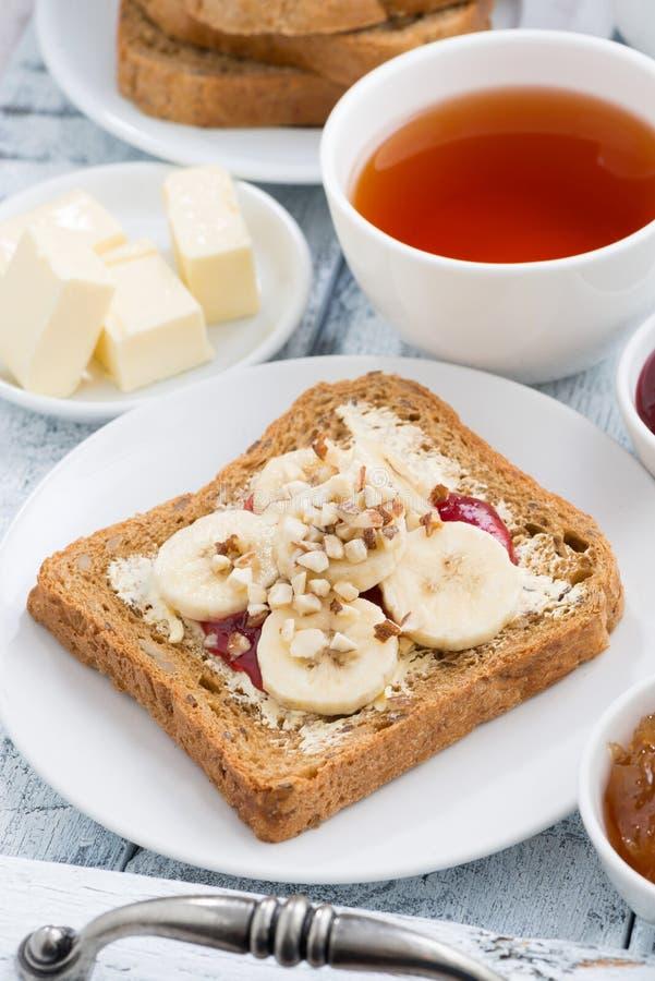 Grzanka z masłem orzechowym i bananem, świeża czarna herbata, zbliżenie obrazy royalty free