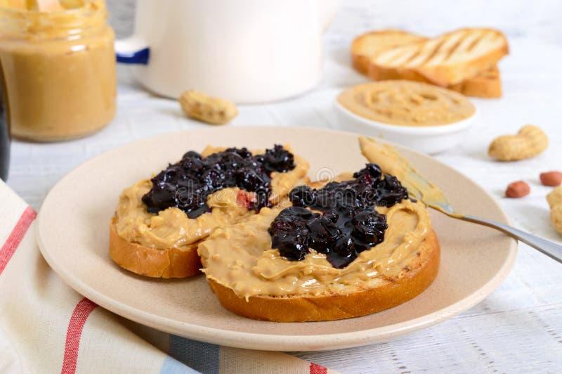 Grzanka z masłem orzechowym i jagodowym dżemem na talerzu, herbata zdjęcia royalty free