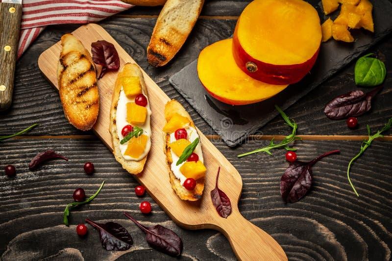 Grzanki z kremowym serem i mango słuzyć na drewnianej desce, nieociosany tło, odgórny widok, kopii przestrzeń zdjęcia stock