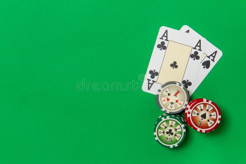 Grzebaków układów scalonych sterta i karty do gry - dwa as na zielonym stole obrazy royalty free