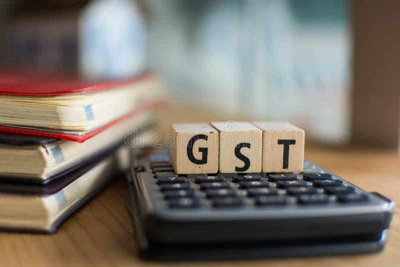 GST的词拼写了与五颜六色的木字母表块 选择聚焦,浅景深 免版税库存照片