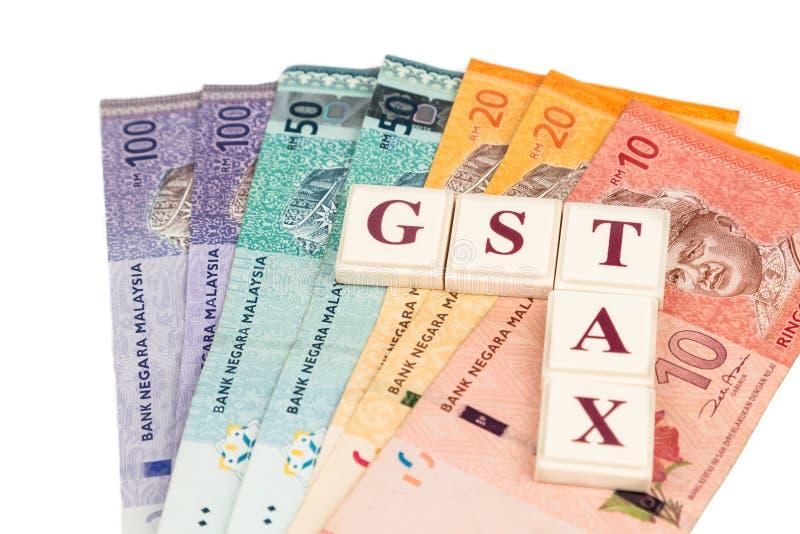 GST-SKATTbegrepp med alfabet från brädeleken och valuta arkivbilder