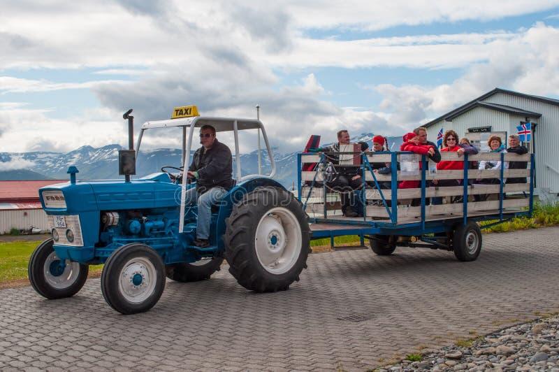 Guía turística que conduce un tractor que tira de un carro con los turistas imagen de archivo libre de regalías