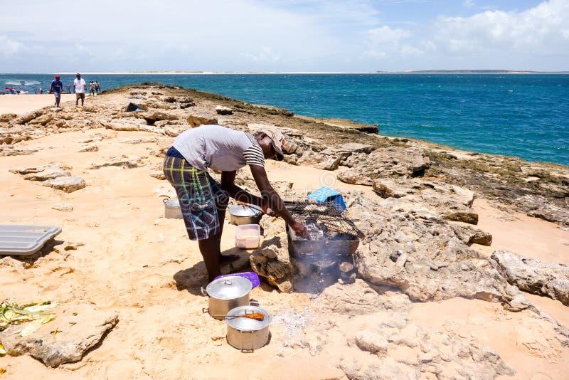 Guía turístico local que asa a la parrilla la barracuda en Mozambique foto de archivo libre de regalías