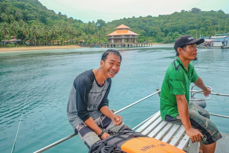 Gu?a tur?stico tailand?s Unacquainted en Koh Chang que sonr?e muy feliz en el barco en tiempo de vacaciones La gente muy disfruta imagen de archivo libre de regalías
