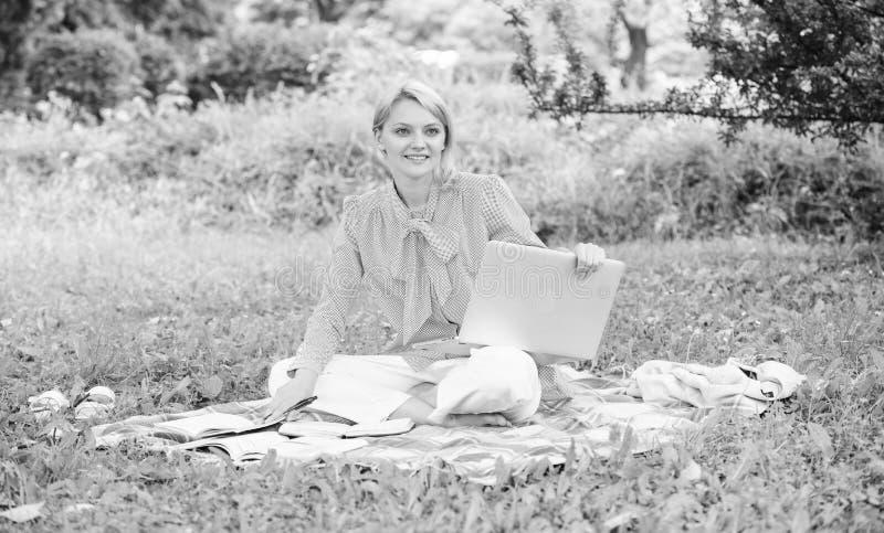 Gu?a que comienza carrera independiente La mujer con el ordenador port?til se sienta en prado de la hierba de la manta Pasos para fotografía de archivo libre de regalías