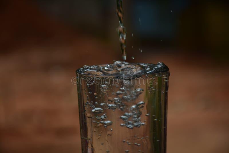?gua de derramamento em um vidro foto de stock