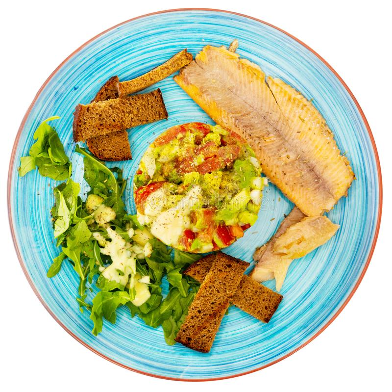 Guacamole with arugula and tomatoes aerved with grilled trout fillet royalty free stock image