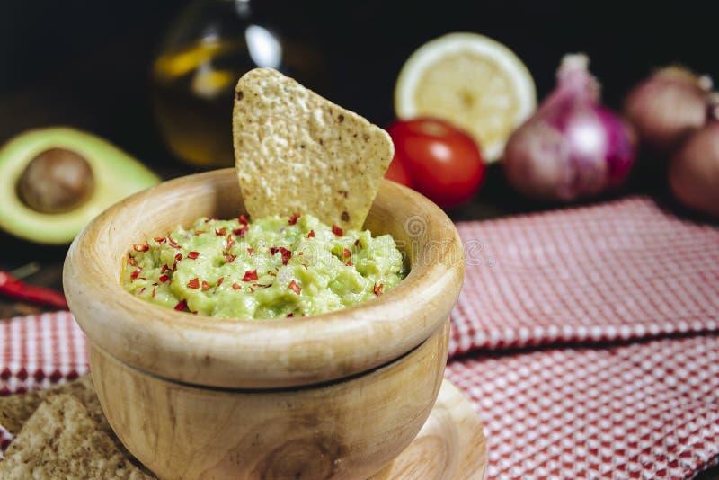 Guacamole avec des nachos à côté des ingrédients frais image stock