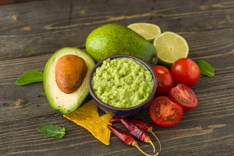 Guacamole in blue bowl on natural rustic desk with ingredient: lemon, tomatoes, peppers around. stock photos