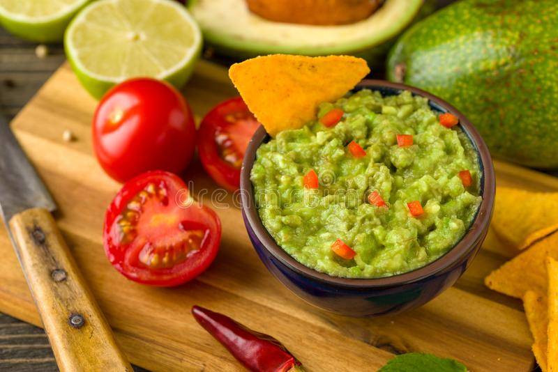 Guacamole in blue bowl on natural rustic desk with ingredient: lemon, tomatoes, peppers around. stock photography