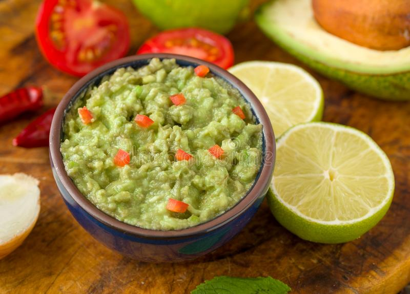 Guacamole in blue bowl on natural rustic desk with ingredient: lemon, tomatoes, peppers around. royalty free stock photography