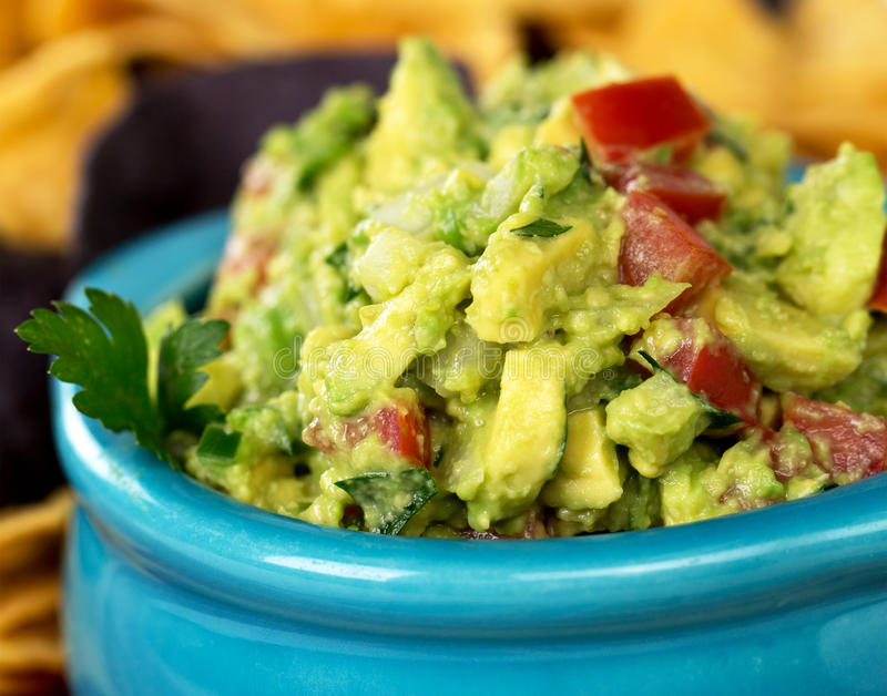 Guacamole 1. A bowl of fresh guacamole with corn tortilla chips. Intentional shallow depth of field stock images