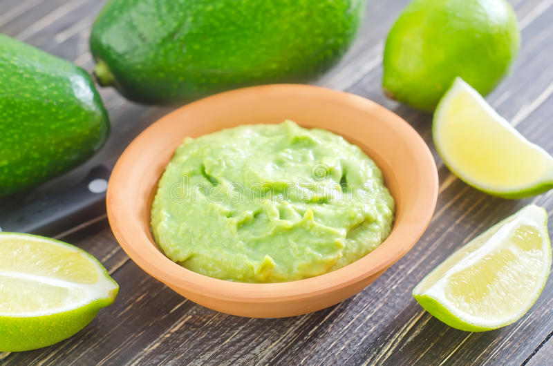 Guacamole. In bowl and fresh fruits royalty free stock images