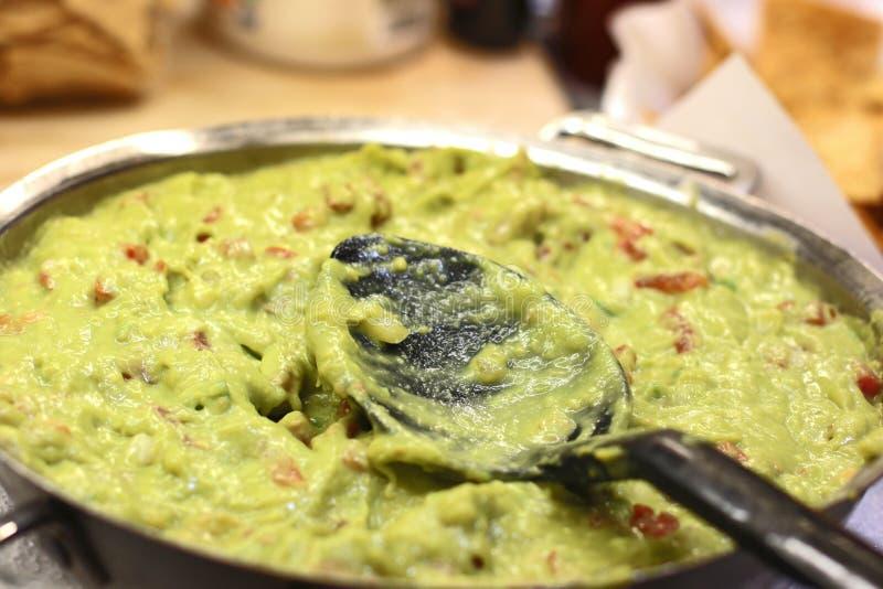 Guacamole. Closeup of a spoon in a bowl with fresh guacamole stock photos
