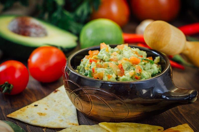 Guacamole com microplaquetas de milho - nachos, feitos do abacate, dos tomates e do cal imagens de stock royalty free