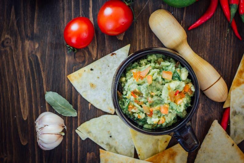 Guacamole con i chip di cereale - nacho, fatti dall'avocado, dai pomodori e dalla calce fotografia stock