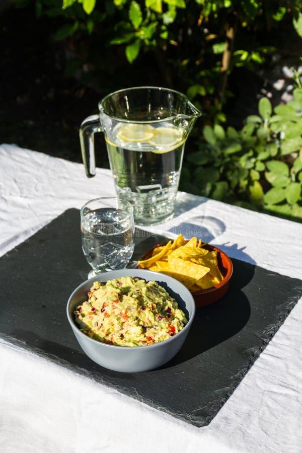 Guacamole dans la cuvette avec de l'eau les puces de tortilla et glacé Dehors o photo libre de droits