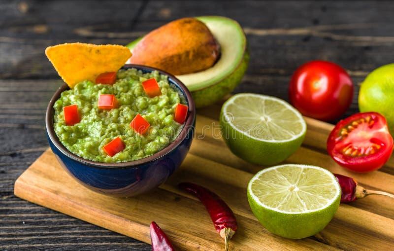 Guacamole dans la cuvette bleue avec les frites et le citron de tortilla sur le bureau en bois naturel photos stock