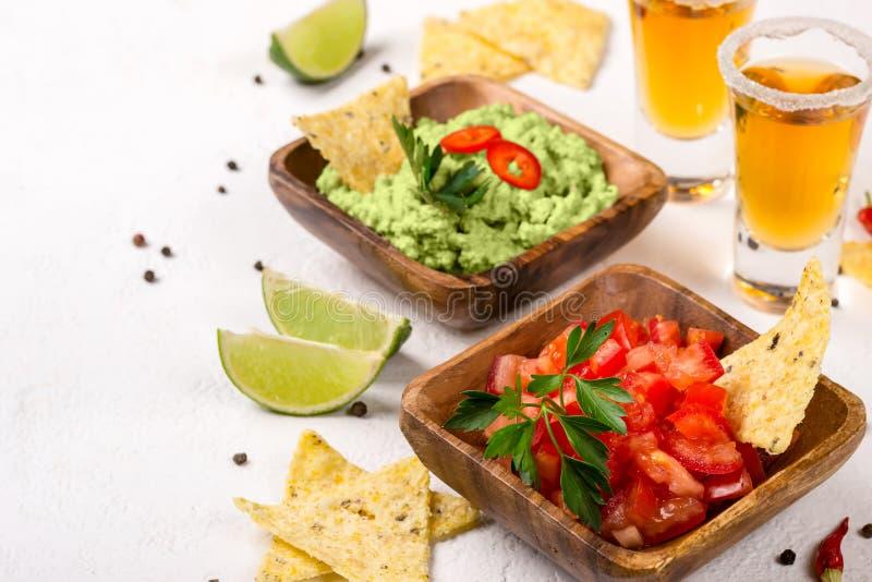 Guacamole do molho do alimento, salsa, microplaquetas e tiros mexicanos do tequila com cal Foco seletivo foto de stock royalty free