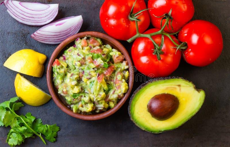 Guacamole e ingredientes - aguacate, tomates, cebolla, fondo de la oscuridad del cilantro fotos de archivo libres de regalías